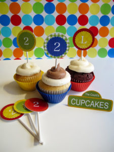 "Print off the cupcake toppers found in the printable section of the party guide. Using a 2"" circle punch or a pair of scissors, cut out the toppers and tape to a lollypop stick (found at craft stores). Stick into your cupcakes for a colorful addition to any table. Our party guide also includes the recipe to these delicious Oreo Cookie Cupcakes!"