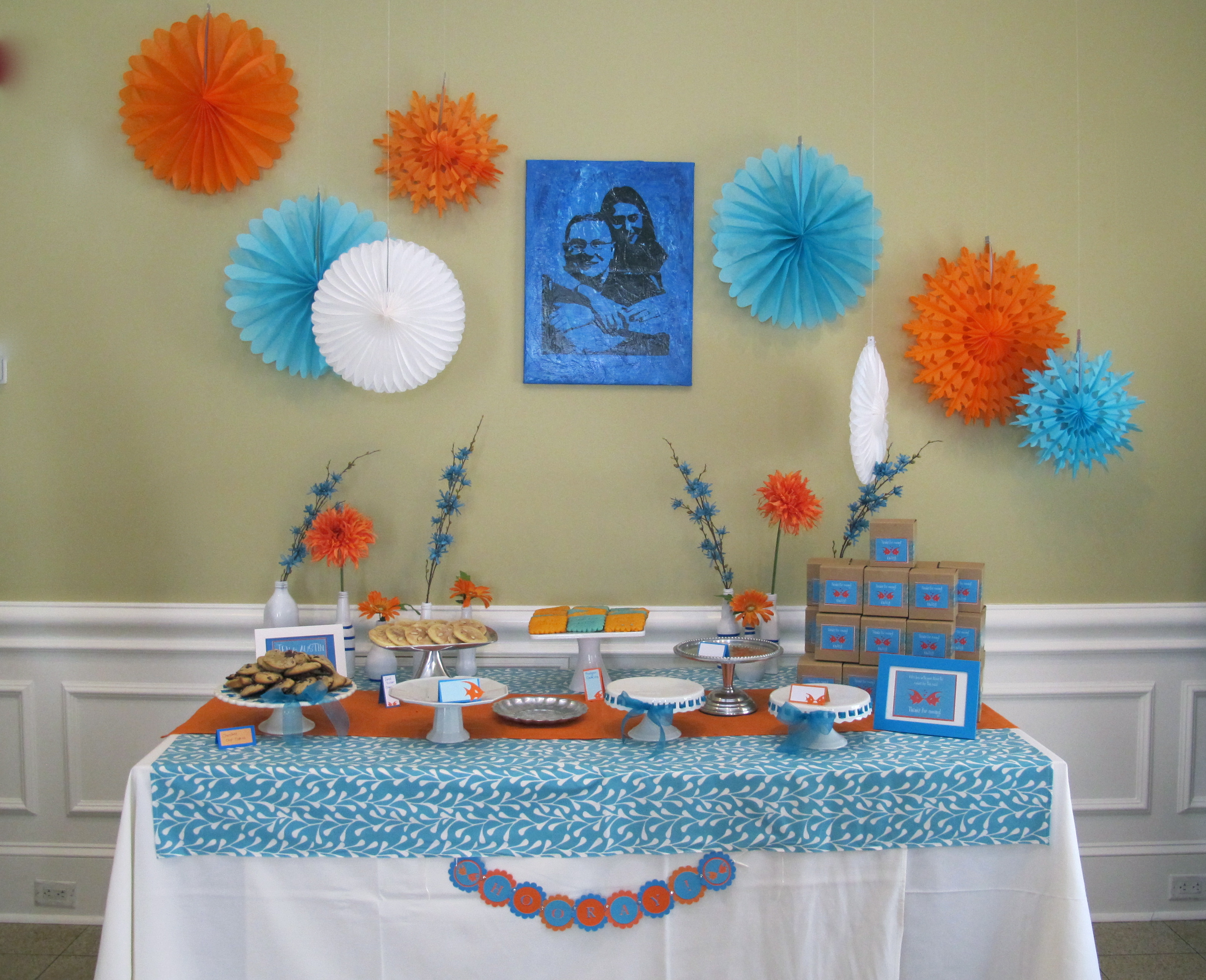 This party was a lot of fun to decorate for. The groom's favorite color is orange (go Texas!) and so we used orange and blue as the main colors. The shower was at a beautiful restaurant, so the only thing we did was the dessert table and the guest's tables. We collected glass vases and jars and spray painted them all white, then added blue artists tape to give them some fun lines. Orange and blue flowers were picked up at a local craft store and added to the vases, which sat behind the dessert table.