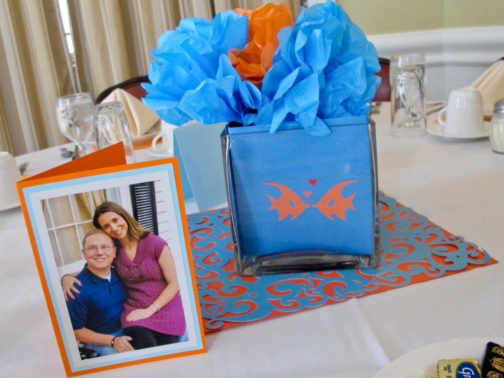 we made 'fish bowls' for each table using blue paper and tiny fish cut-outs in glass vases. Tissue paper flowers were put inside, and the pictures from the couples engagement session were displayed on tables around the room.