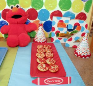 Elmo Party Decorations | We turned an ordinary kitchen island into a colorful party table by making this polka-dot backdrop. Add in balloons, festive table-wear, and lots of party food for a great 'Elmo's World' kids party!