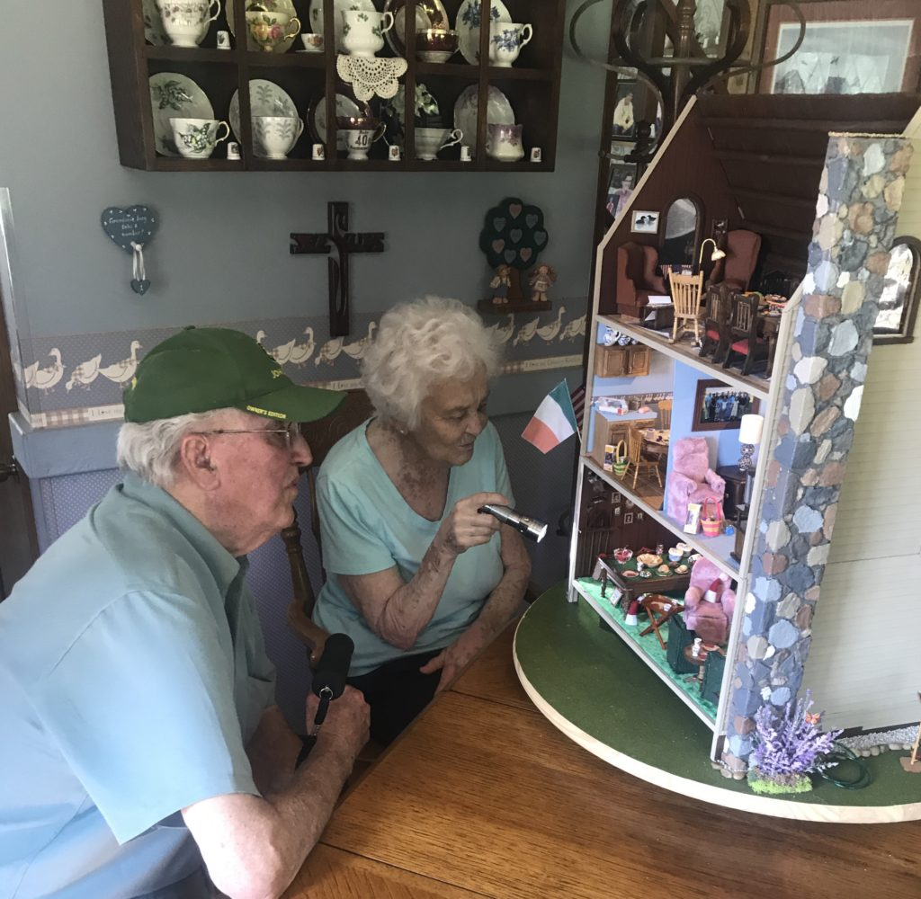 Grandma and Grandpa looking at heirloom dollhouse for the first time