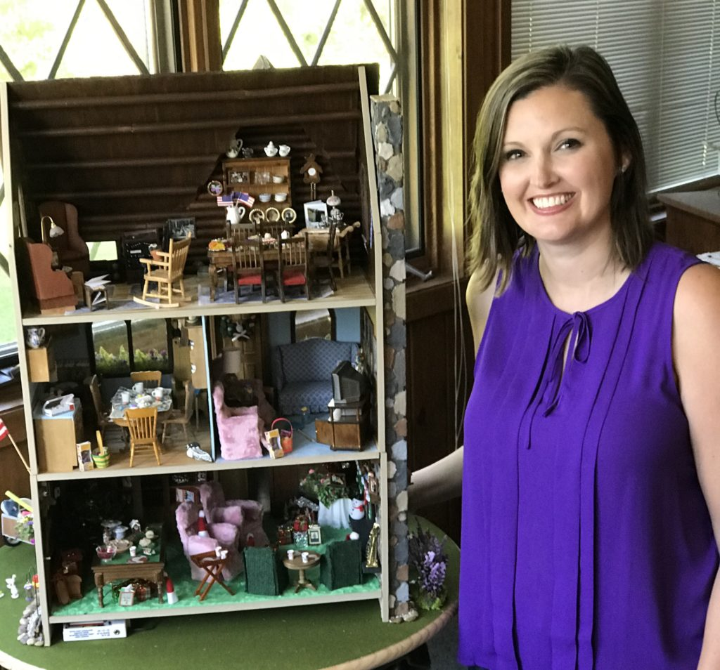 Granddaughter standing with heirloom dollhouse
